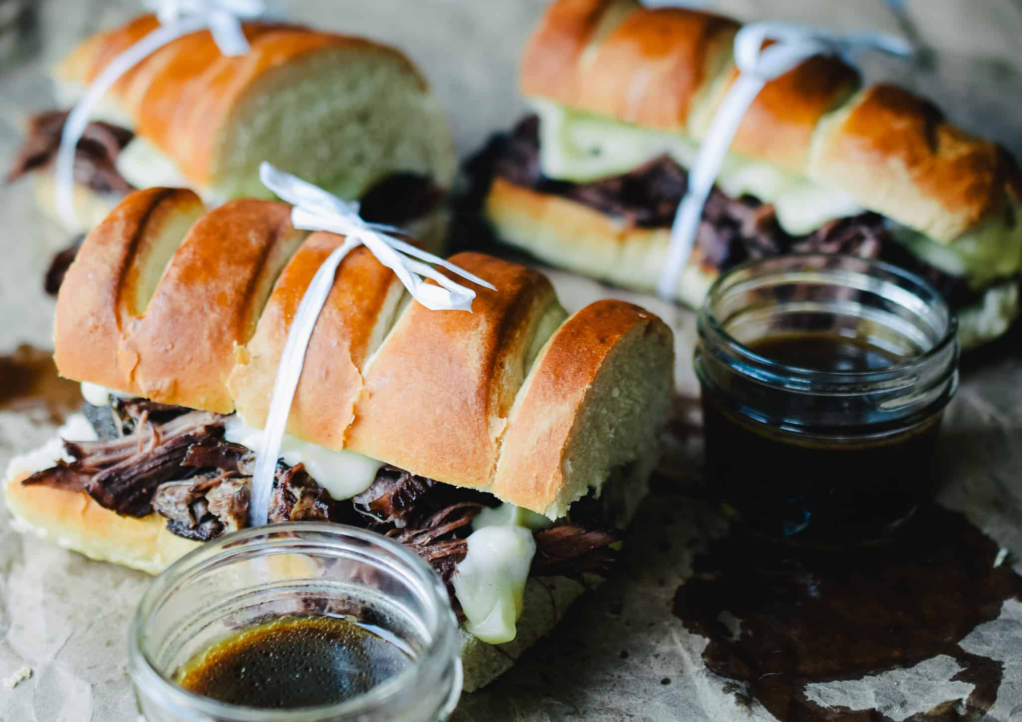 french dip sandwiches tied with white twine on brown paper for serving and a cup of au jus