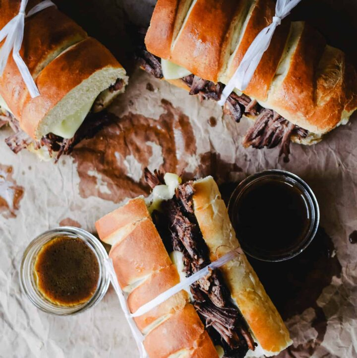 three french dip sandwiches tied with white twine on crinkled brown paper with two cups of au jus