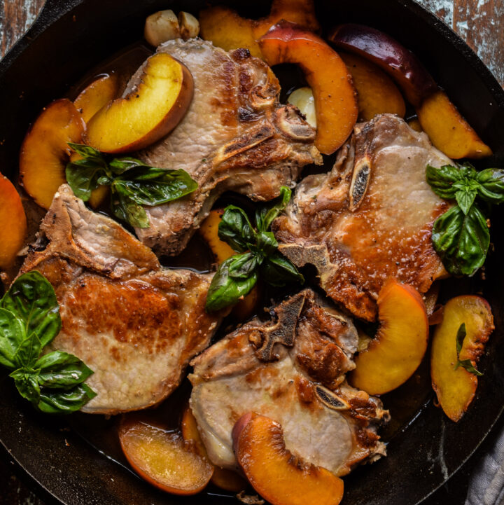 Bone in pork chops in a cast iron skillet with peaches and basil leaves.