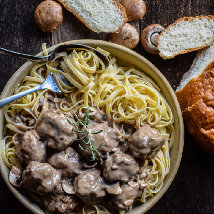 A bed of fettuccine pasta with meatballs in mushroom sauce