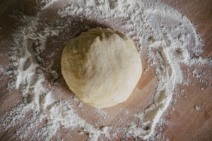 ball of pasta dough on floured wood surface