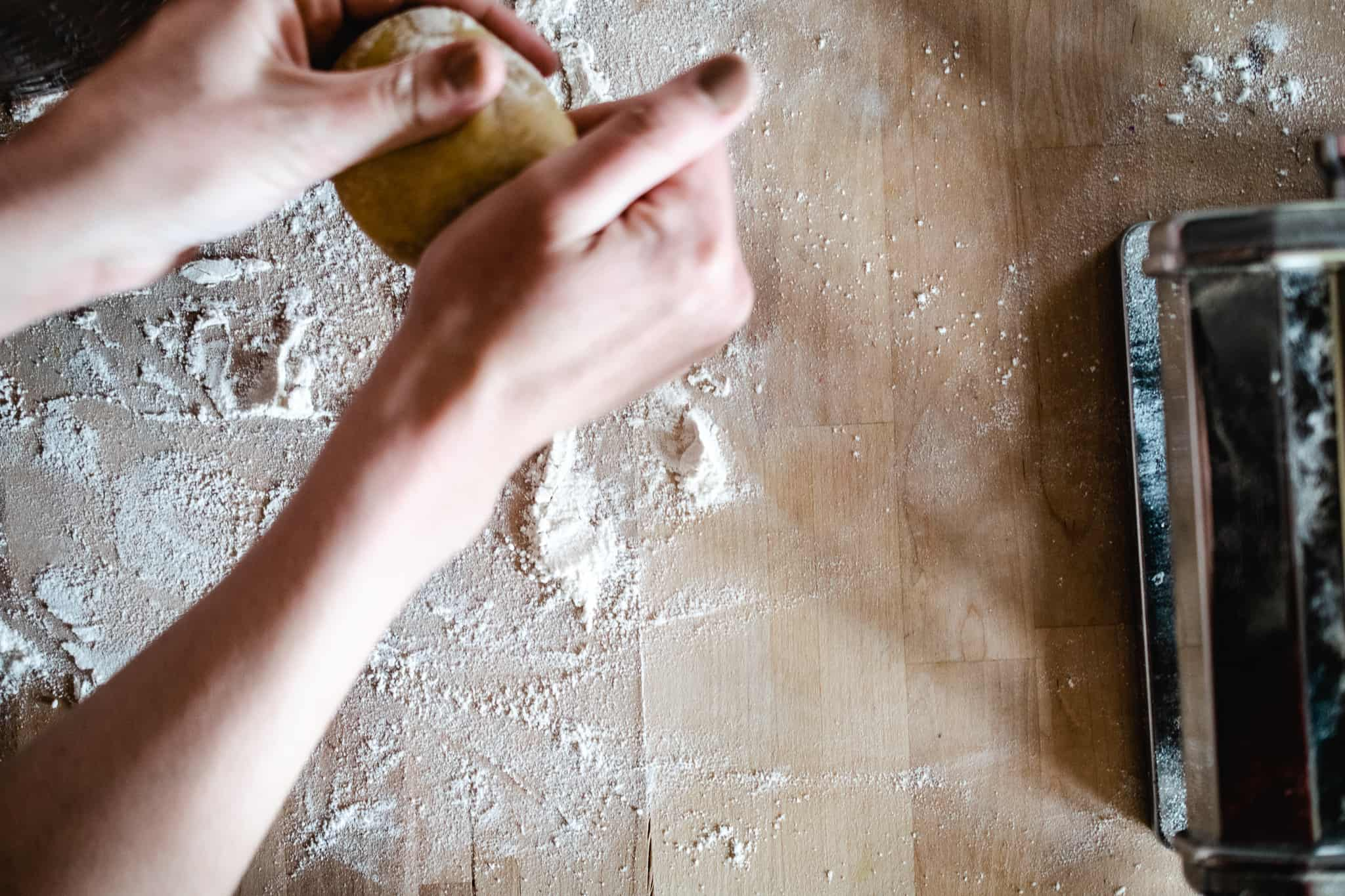 hands forming pasta dough into ball over floured butcher block surface