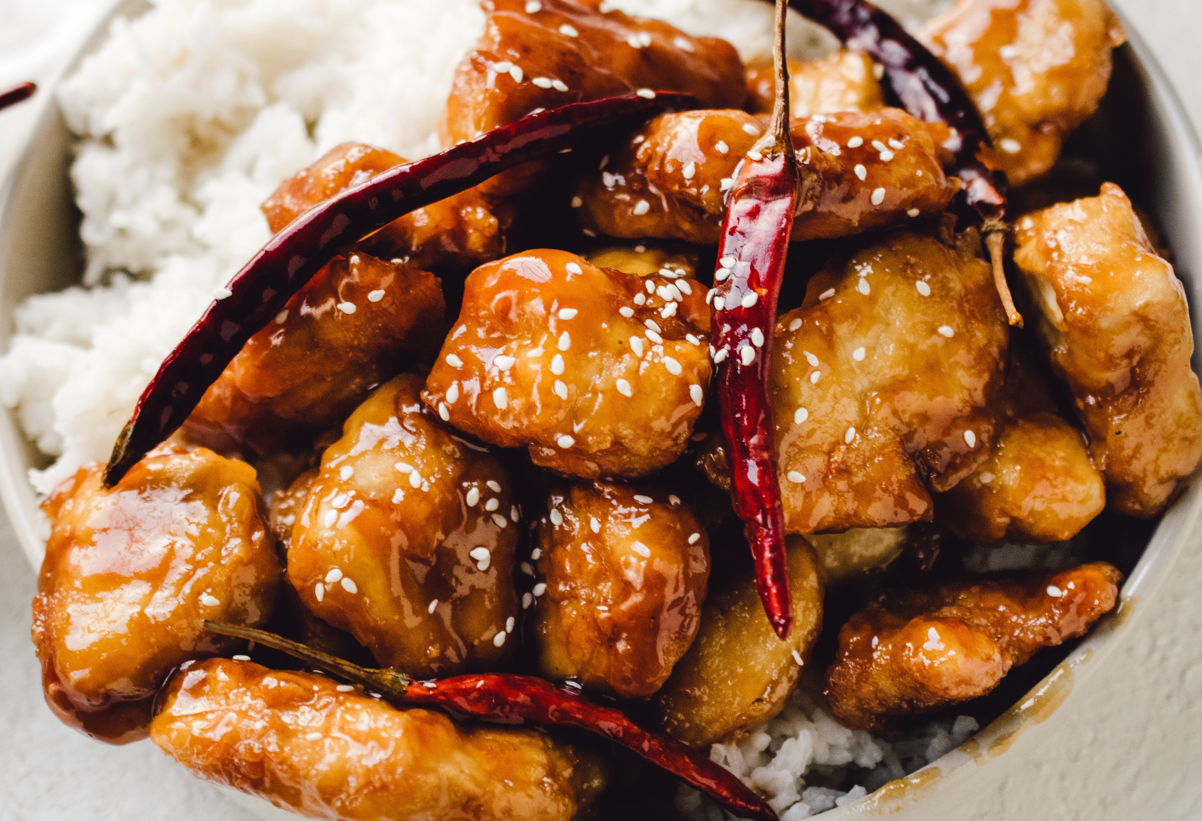 Close up of general tso's chicken with white sesame seeds on a bed of white ricd