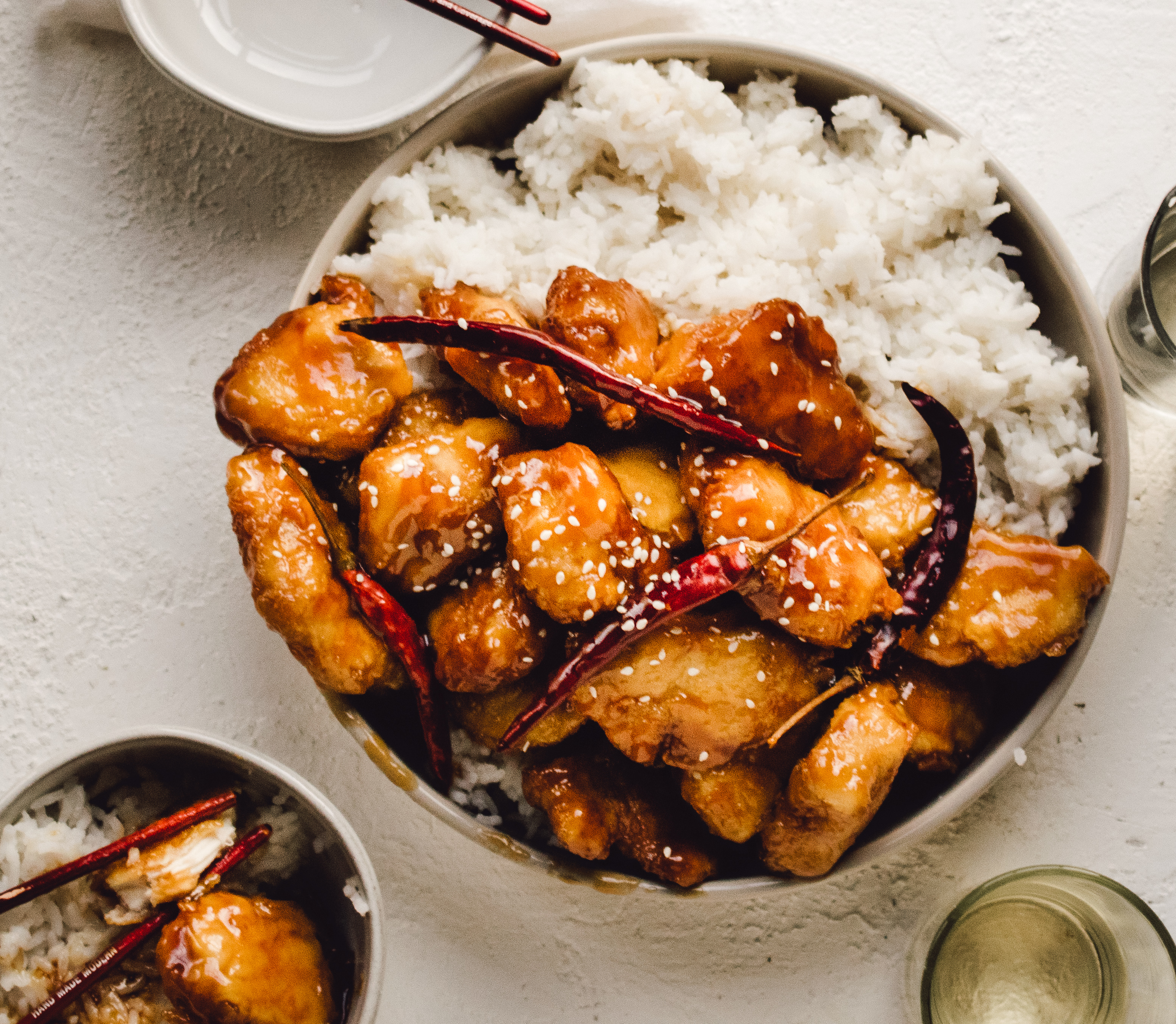 Family style bowl of homemade general tso's chicken with steamed white rice, and extra bowls and chopsticks for serving
