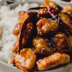 general tso's chicken next to a bed of fluffy white rice served family style in a large gray bowl