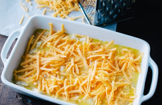 white casserole dish layered with diced potato, beaten egg and shredded cheese