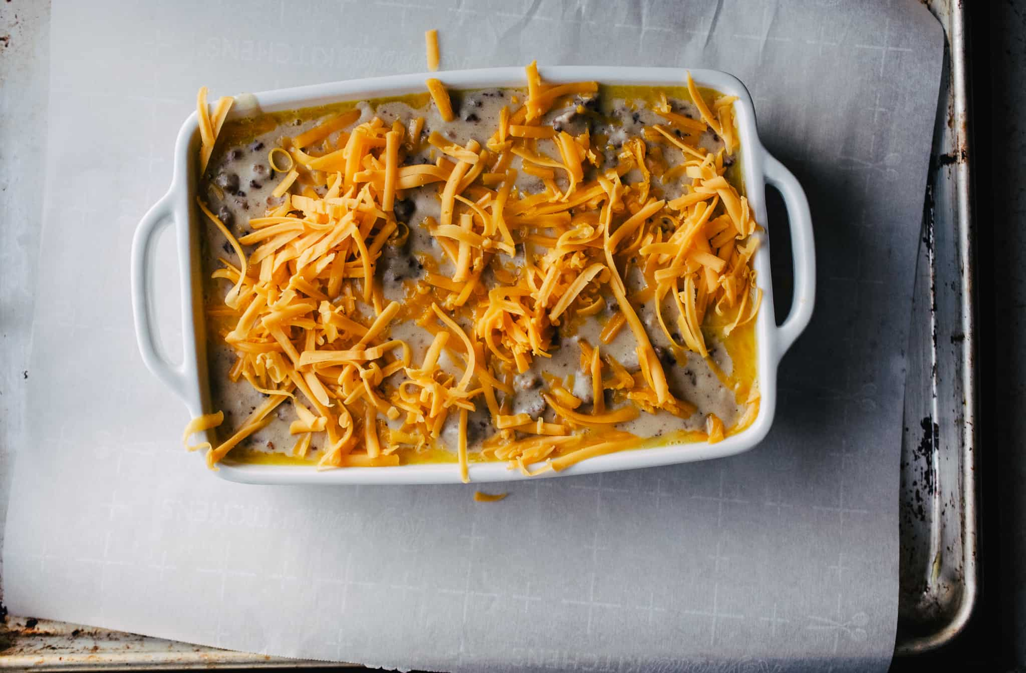 white casserole dish with handles with uncooked shredded cheese topped sausage gravy casserole on parchment paper lined aluminum baking sheet