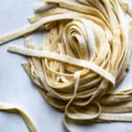 homemade fettuccine pasta ribbons in a nest on a grey surface