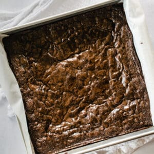 freshly baked brownies with shiny tops in a square pan