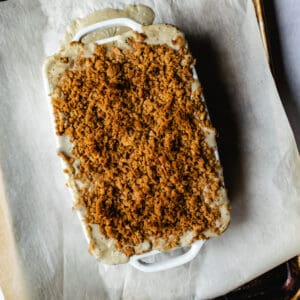 white rectangular casserole dish with two handles filled with crumb topped casserole dish on a baking sheet