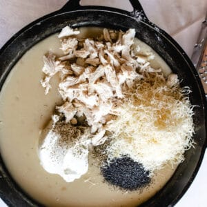skillet with casserole ingredients being added to cream of chicken soup base