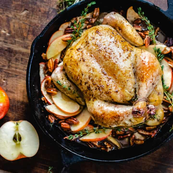 Whole, roasted chicken on a bed of sliced apples with sprigs of thyme in a cast iron skillet.