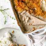 rectangular casserole dish of chicken poppy seed casserole with wooden spoon scooping a serving out