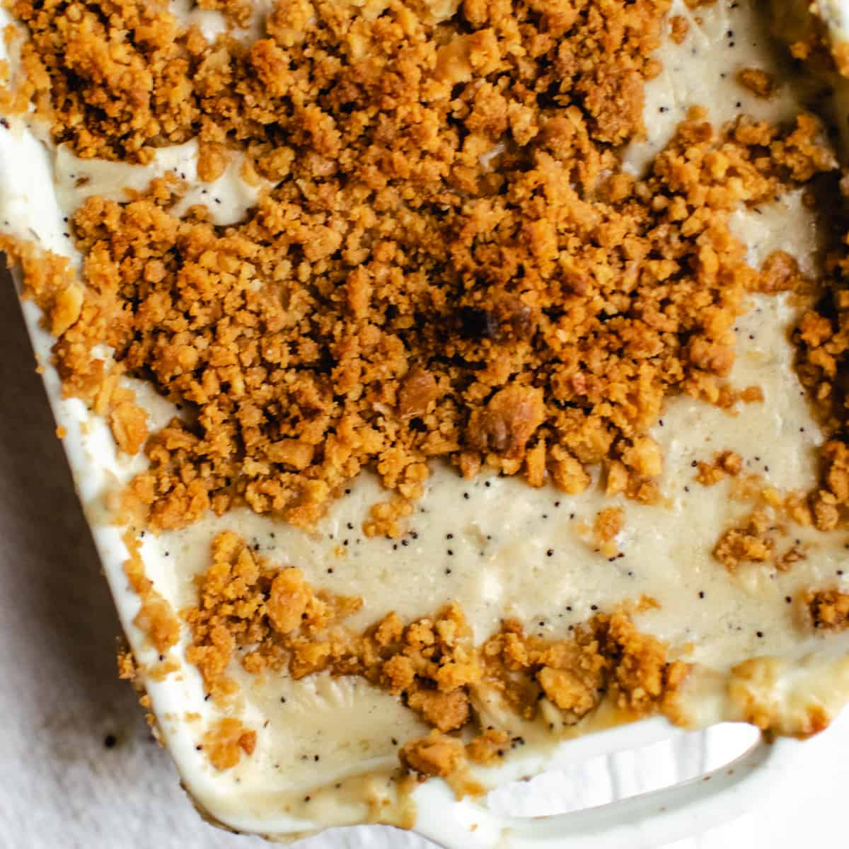 casserole in a white dish with a golden crunchy cracker crumb topping on white background