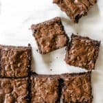 brownie squares with crinkle tops cut into squares on white parchment paper and marble counter top