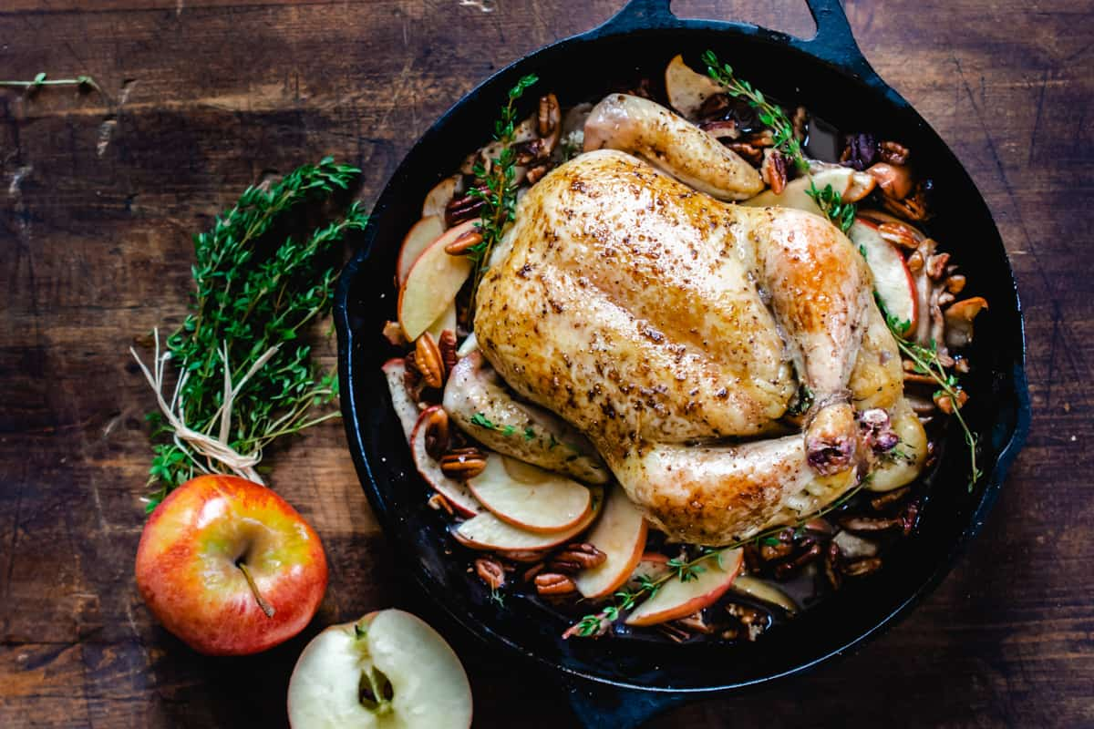 Roasted chicken in a cast iron skillet surrounded by fresh apples an pecans.