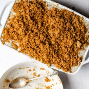 white casserole dish covered with cracker crumb topping next to empty bowl of crumbs