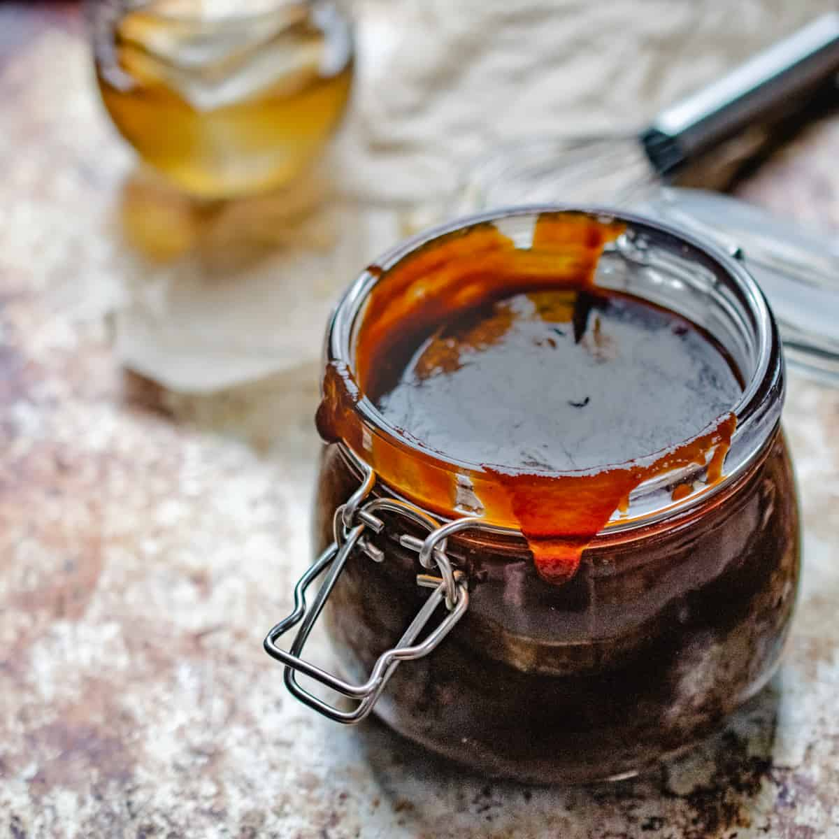 Gasket and hinge jar filled with barbecue sauce with honey on a whisk and glass of bourbon.