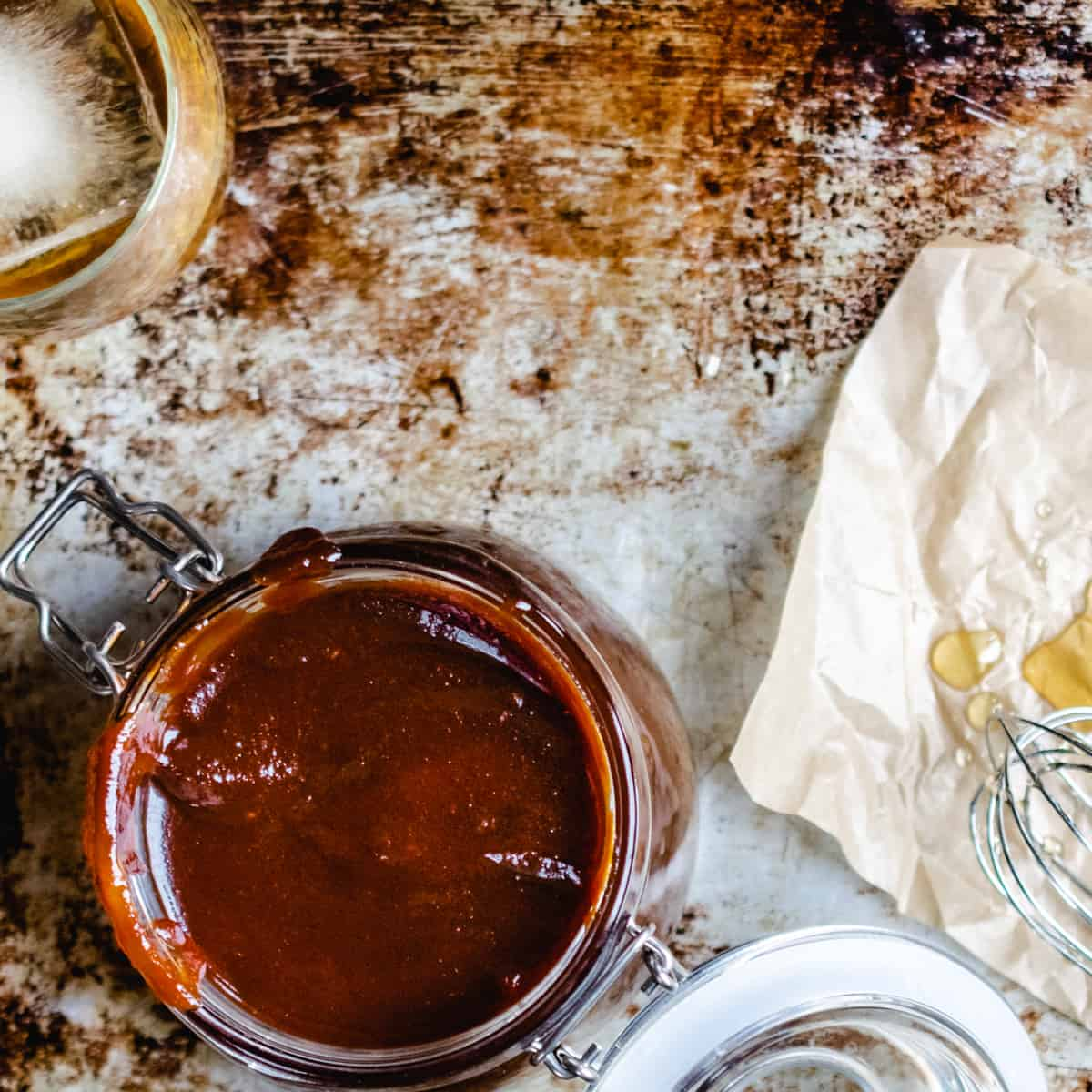 A jar of barbecue sauce next to a whisk with honey on it and glass of bourbon with ice.