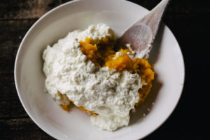 white bowl of roasted butternut squash puree with ricotta cheese and a wooden spoon on a wood surface