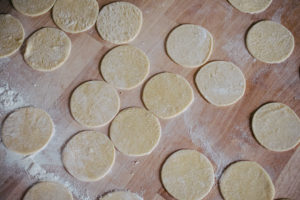 Circles of pasta dough cut out for ravioli on a floured surface