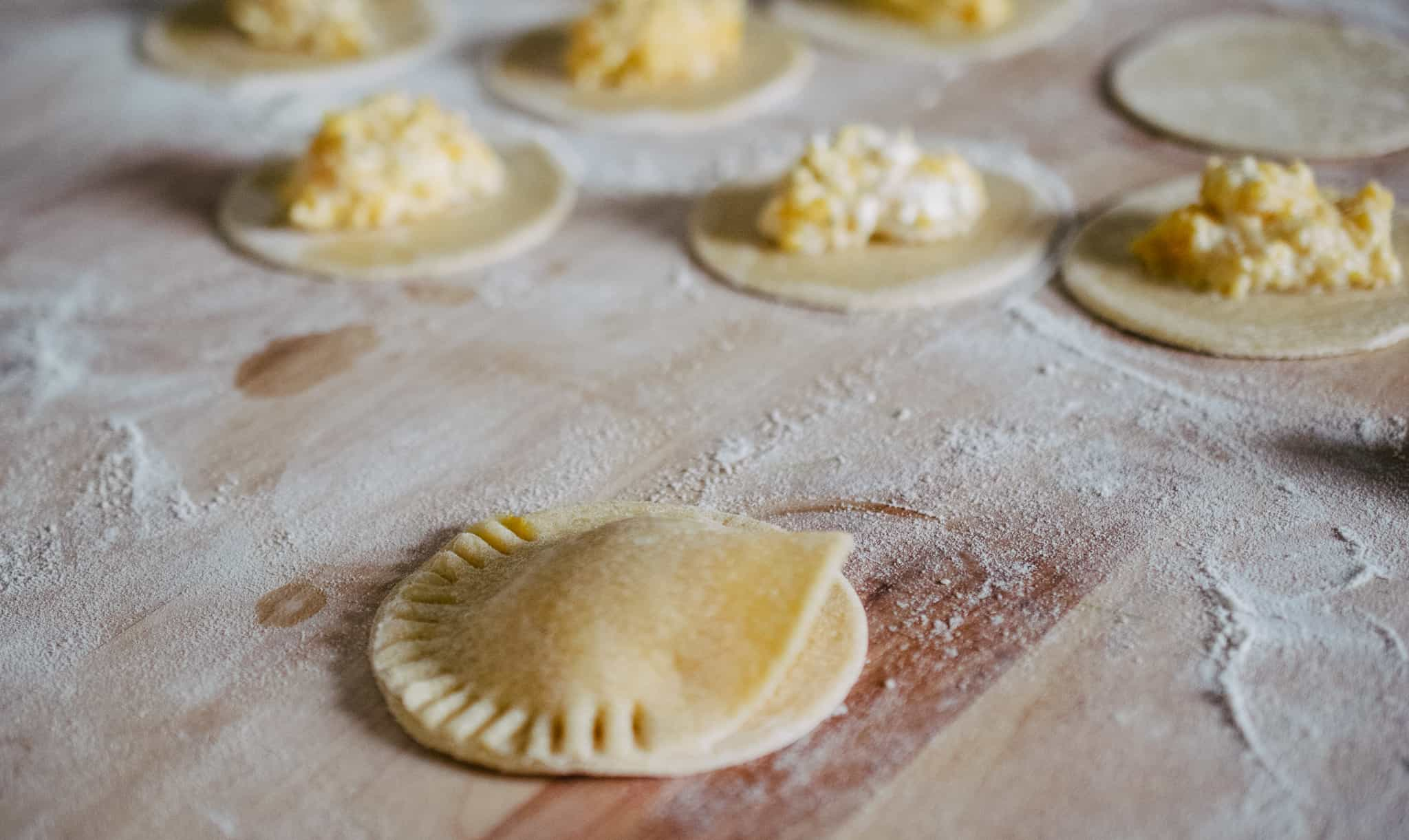 jumbo butternut squash and ricotta ravioli dough being stuffed and sealed on a floured, butcher block counter top