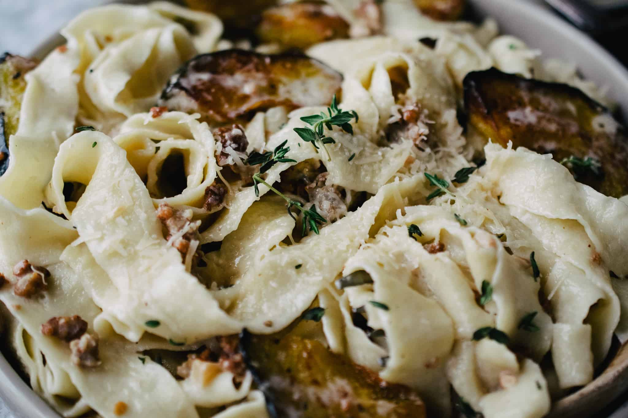 pappardelle pasta tossed with acorn squash wedges in a sherry cream sauce with parmesan cheese and thyme sprigs