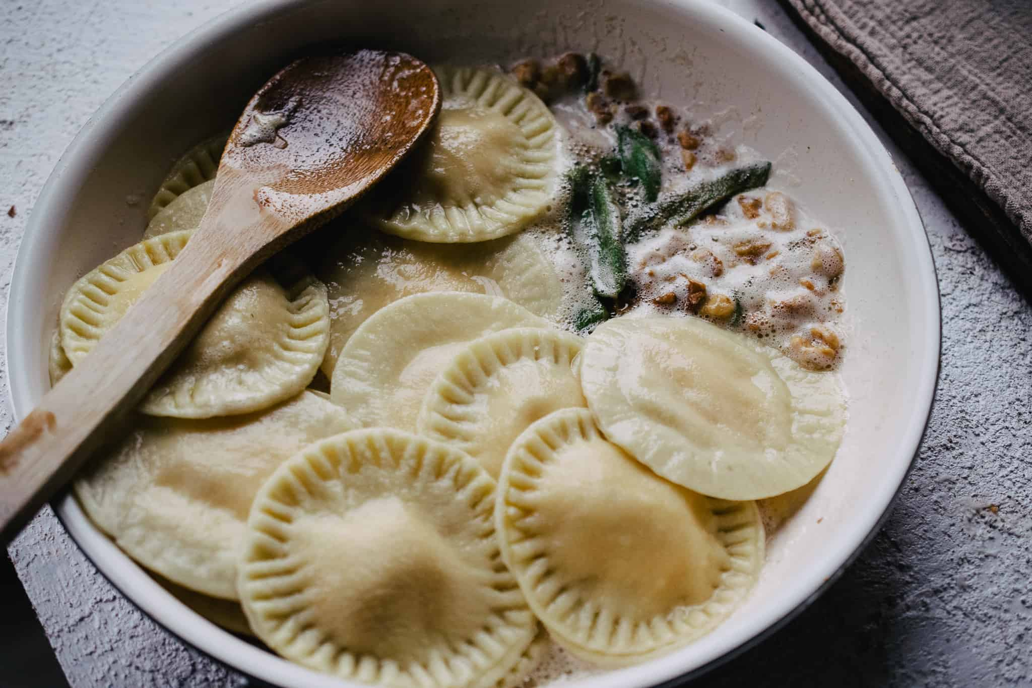 freshly cooked raviolis added to a skillet of browned butter, walnuts and fried sage about to be tossed and combined with a wooden spoon
