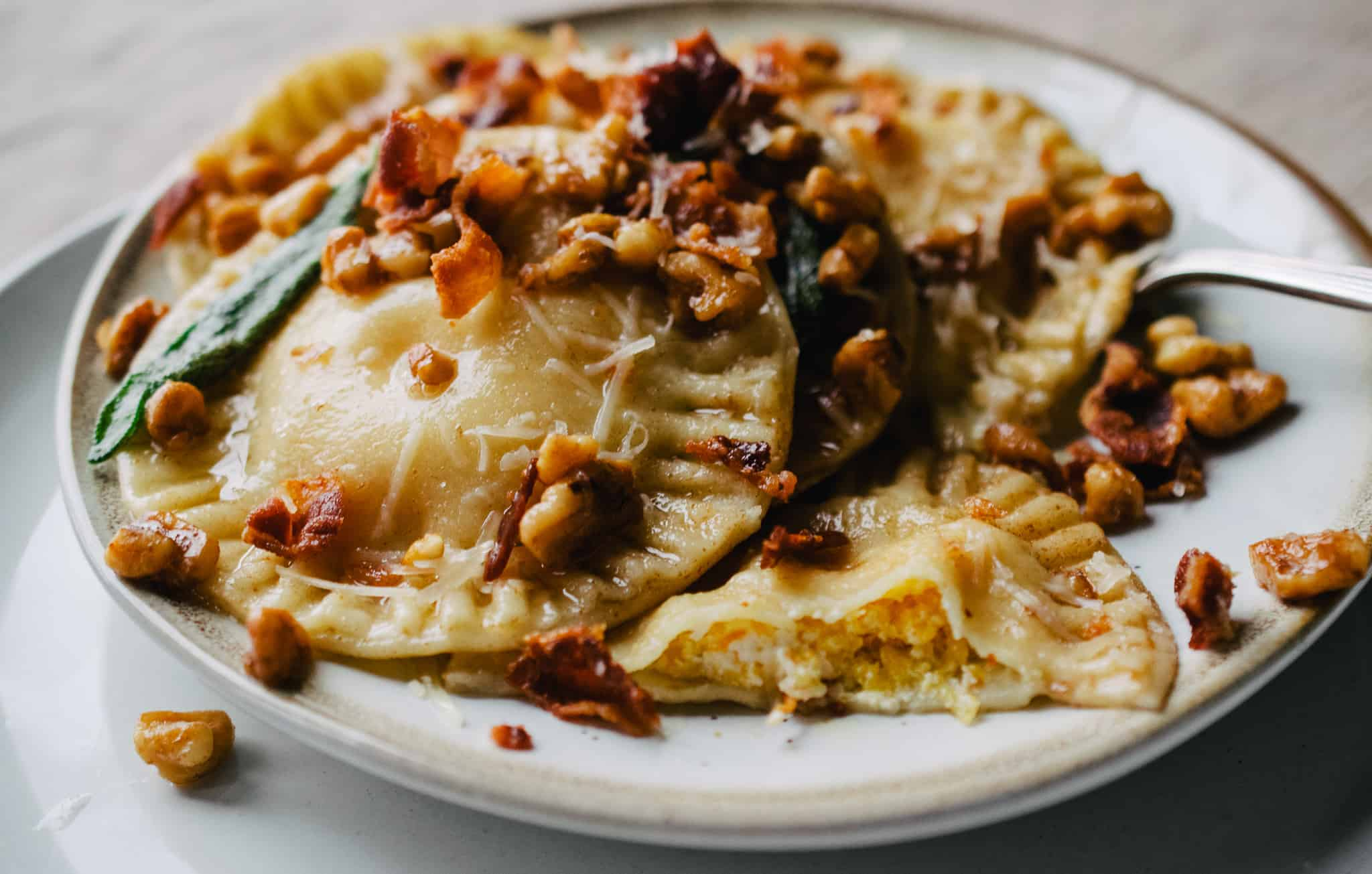 stoneware plate of butternut squash handmade ravioli with fried sage and walnuts on linen tablecloth