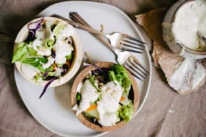 two wooden bowls of salad with ranch dressing poured over on stoneware plate with two forks on brown flour sack cloth