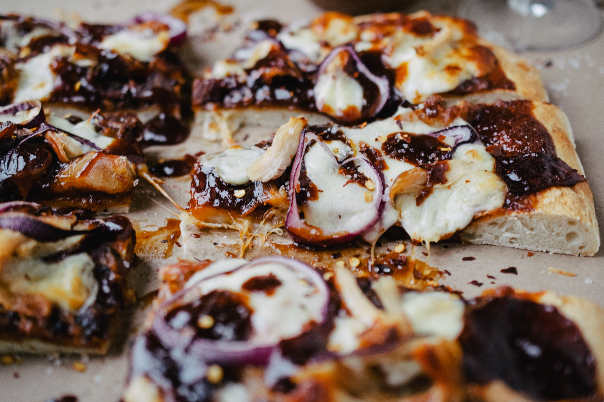 piece of barbecue chicken flatbread with crushed red pepper flake on brown paper
