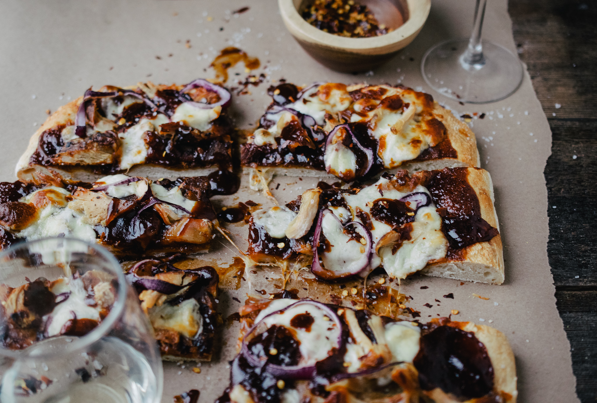 barbecue chicken flatbread with crushed red pepper flake on brown paper with two glasses of white wine on wood table top