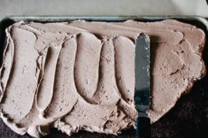 chocolate sheet cake being frosted with chocolate frosting
