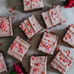 chocolate sheet cake with red and pink frosting on brown paper with red carnations