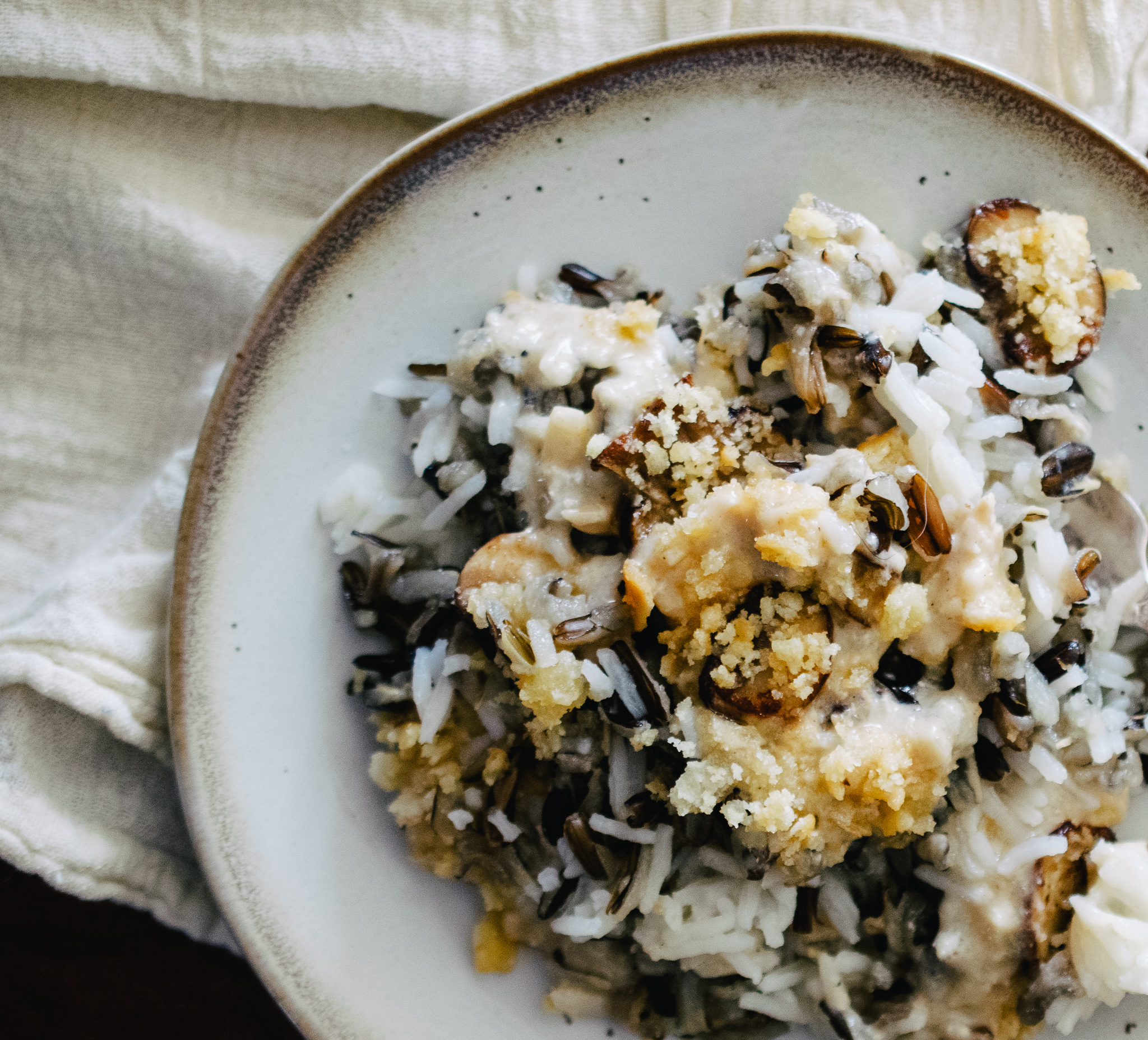 irregular round white plate with brown speckles and brown rim with creamy and cheesy wild rice and mushroom casserole, on a tan flour sack cloth