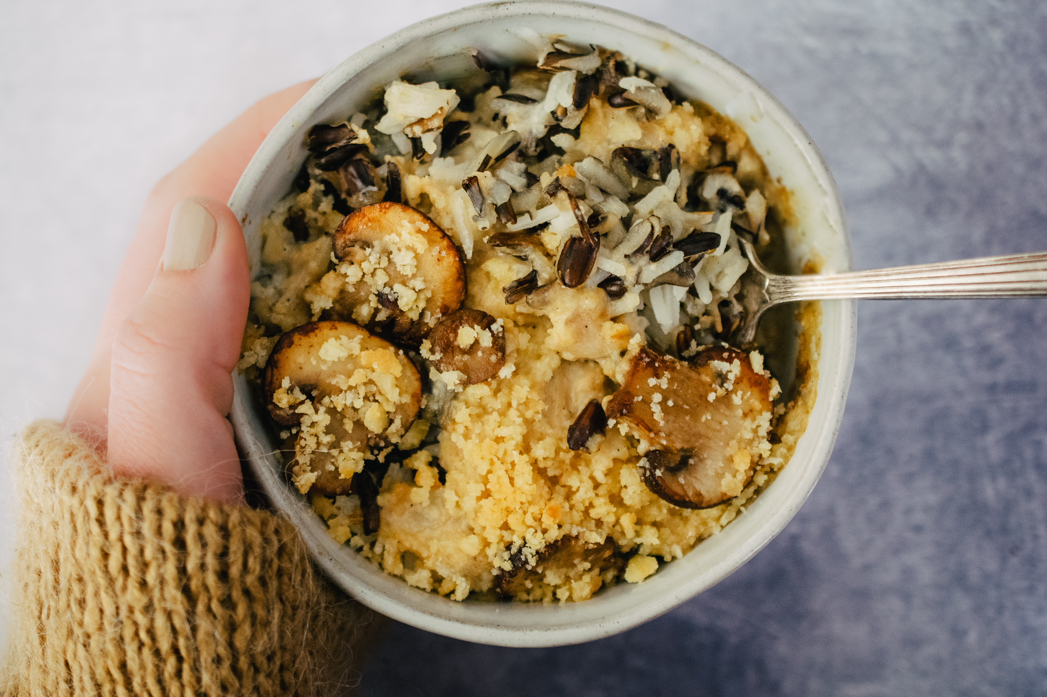 hand with tan sweater holding an irregular white stoneware bowl of mushroom and wild rice casserole with an antique fork