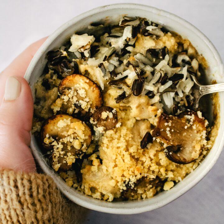 Hand holding a bowl of wild rice mushroom casserole.