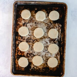 Circle shaped cookie dough cut out and placed on baking sheet.
