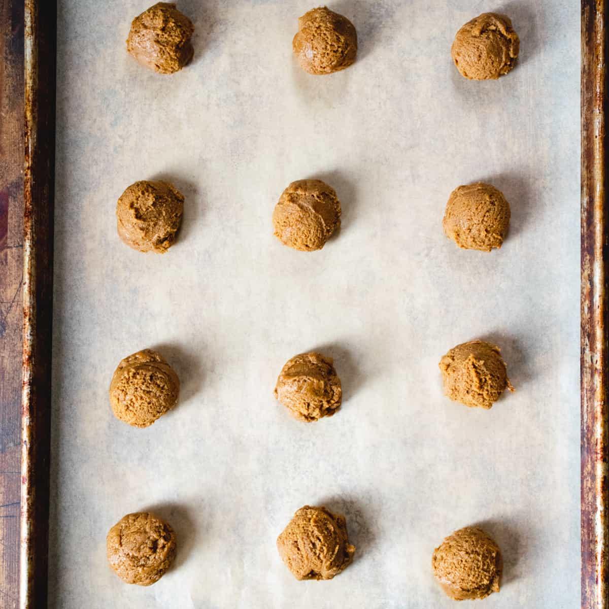 Balls of cookie dough on a baking sheet.