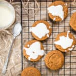 Ginger molasses cookies with a bowl of white icing on a baking with twine.