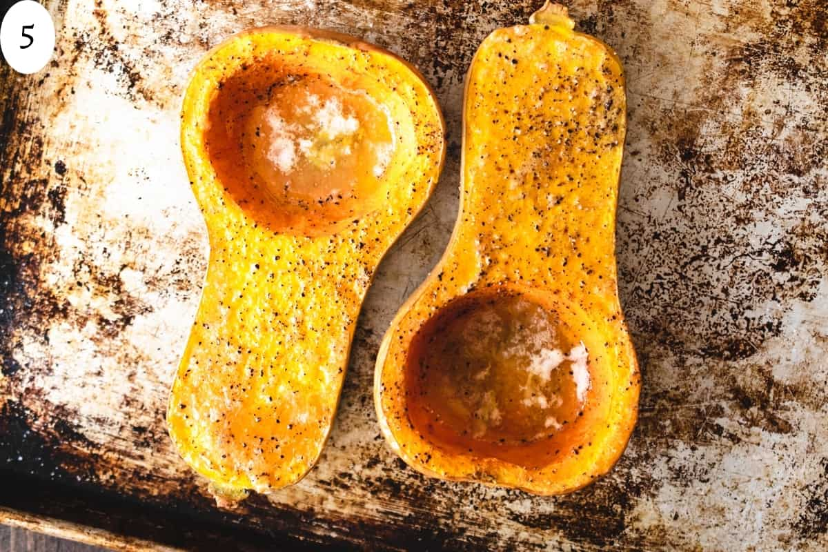 Two roasted butternut squash halves on an aluminum baking sheet.