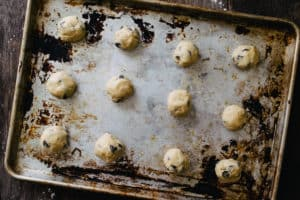 aluminum baking sheet with raw balls of chocolate chip cookie dough on a wood surface