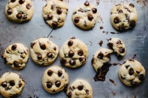 aluminum baking sheet of warm chocolate chip cookies, with the melted chocolate chips and one cookie split in half