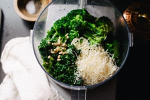 food processor with leafy greens, parmesan cheese and pine nuts
