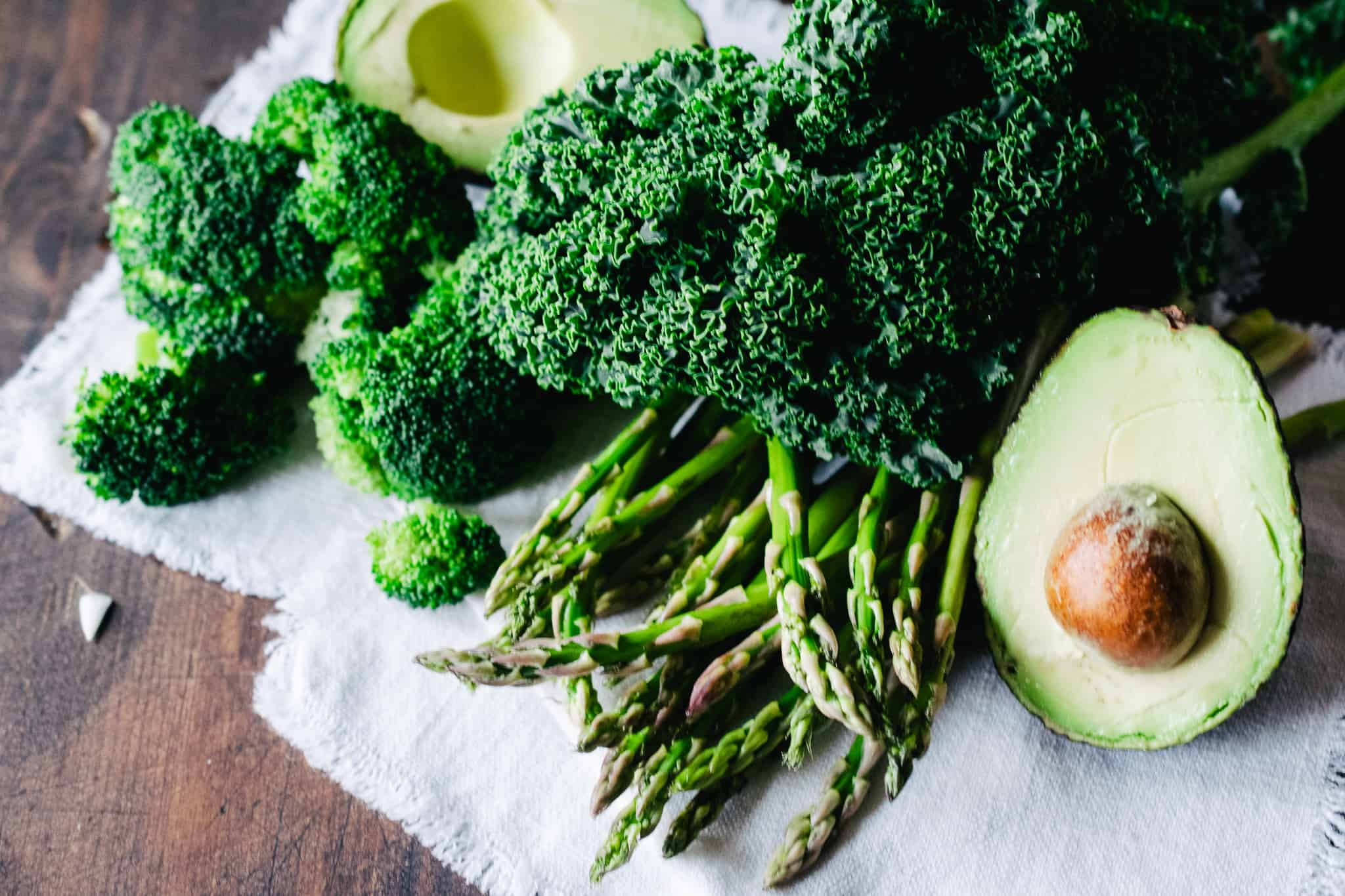 leafy green vegetables, broccoli, kale and avocado on dark wooden table