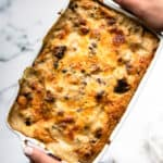 white handled casserole dish of layered sausage gravy, cheese, egg and potatoes
