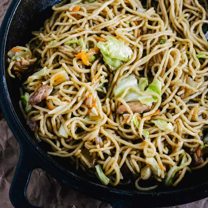 Stir fried noodles with cabbage, onion and carrots in a cast iron skillet.