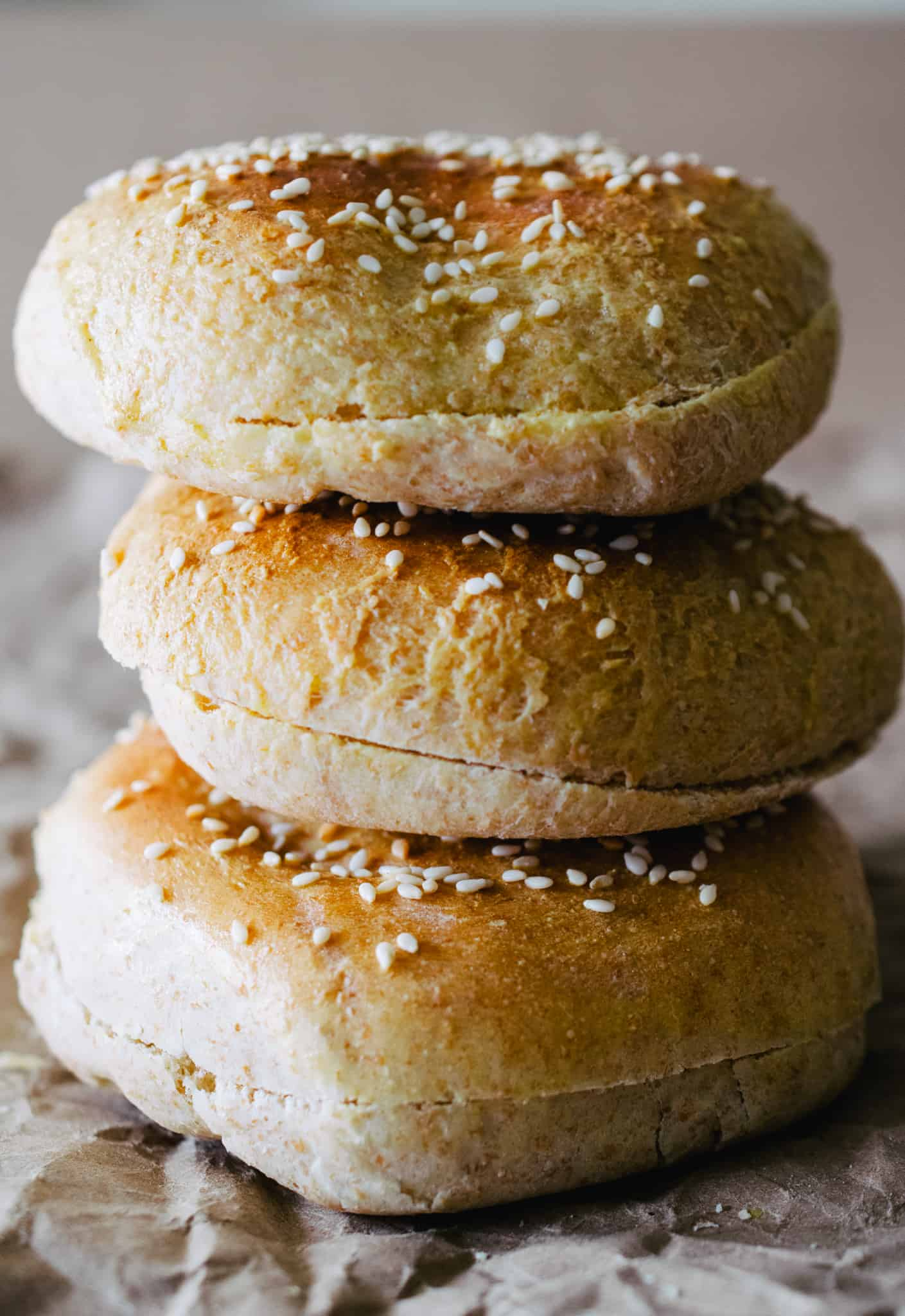 3 homemade sesame seed hamburger buns stacked on top of each other on brown paper surface and background