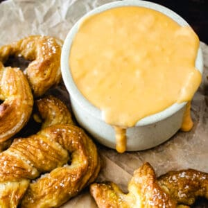 Ramekin of beer cheese by a salted soft pretzel on parchment paper.