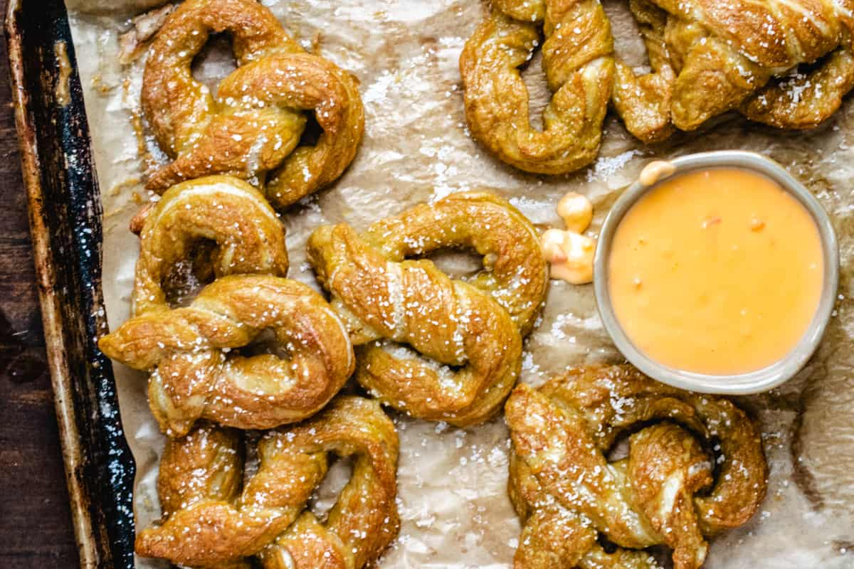 Ramekin of beer cheese on a tray of salted soft pretzels.